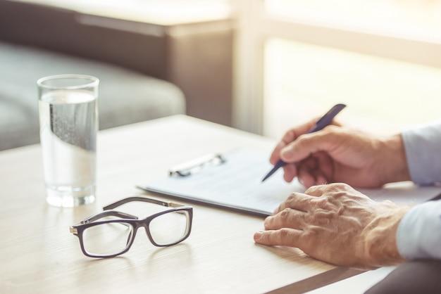 中年の心理療法士の手がメモを作っています