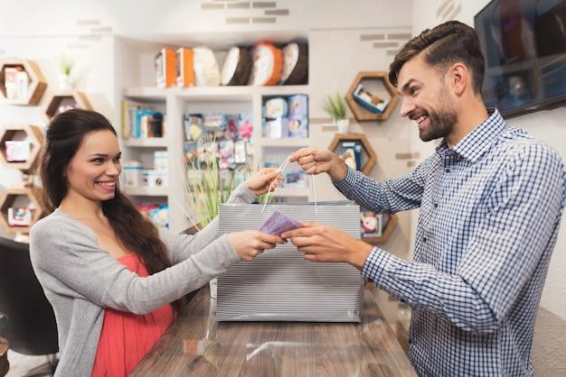 妊娠中の女性が店内の売り手にお金を渡します。