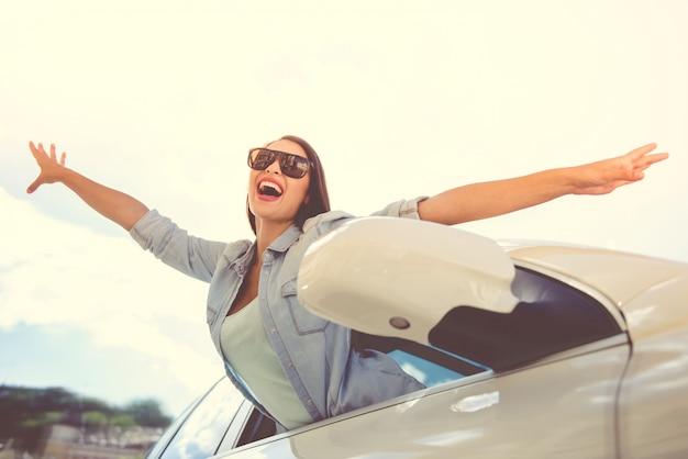 Счастливая девушка в стильной одежде и солнцезащитных очках