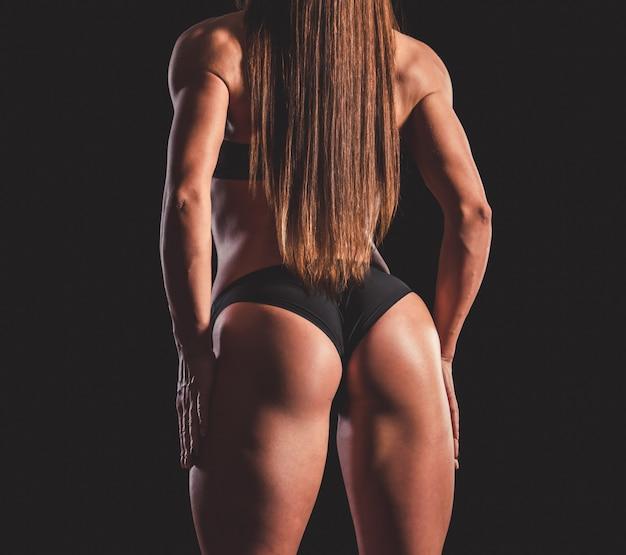 Сильная мускулистая женщина в черном нижнем белье
