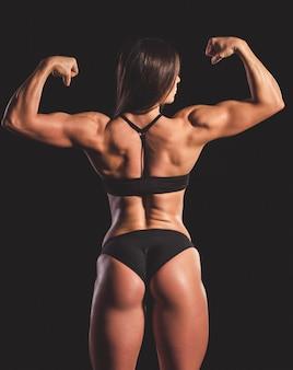 Женщина в черном нижнем белье, показывая ее мышцы