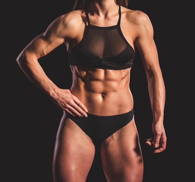Женщина в черном нижнем белье показывает ее мышцы живота