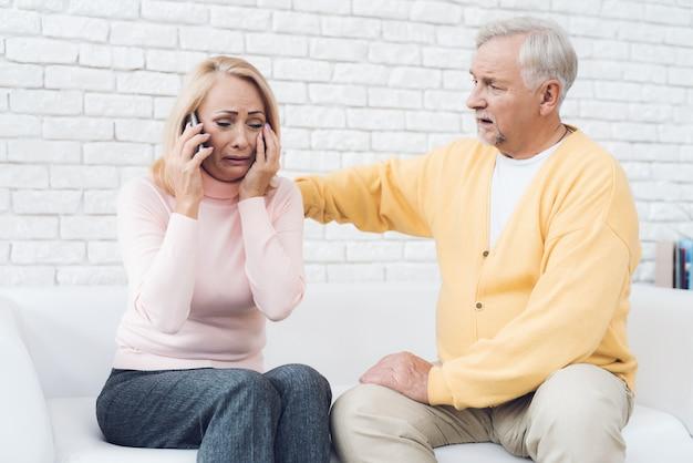 Расстроенная старая женщина разговаривает по смартфону возле старика