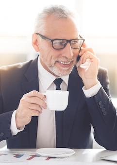 成熟した実業家はカップを保持しています。