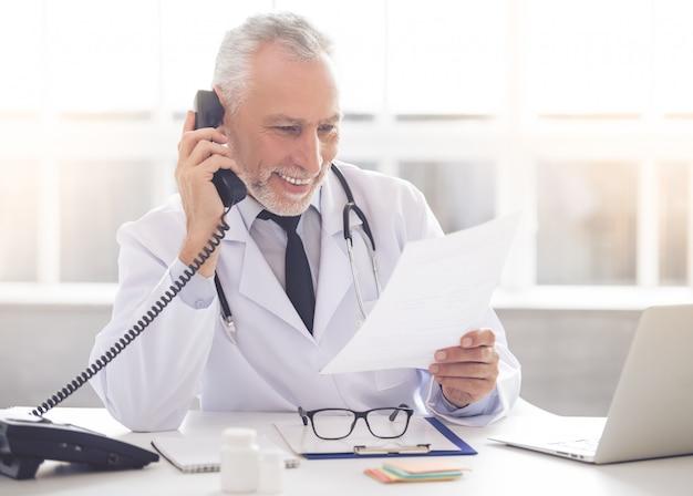 白衣の医者は電話で話しています。