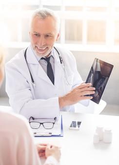 白衣の医者はデジタルタブレットを指しています。
