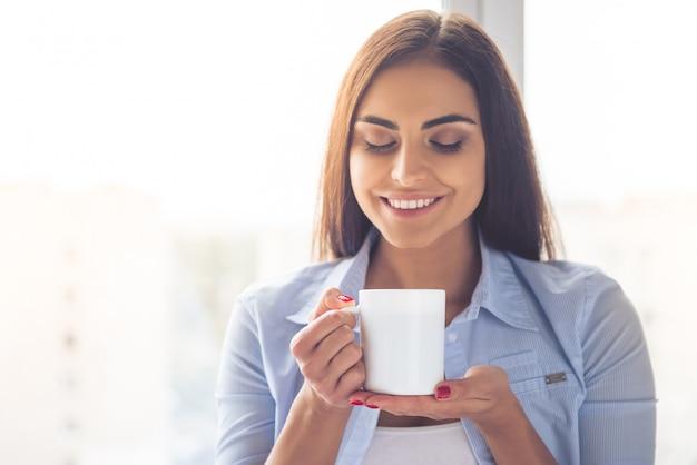 美しいビジネス女性の肖像画はカップを保持しています。
