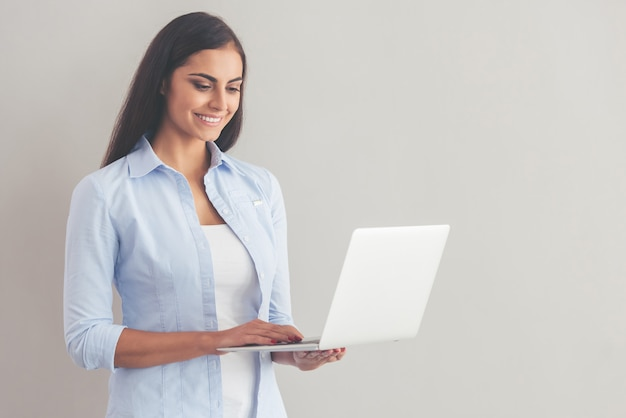 カジュアルな服装で美しいビジネス女性はラップトップを使用しています