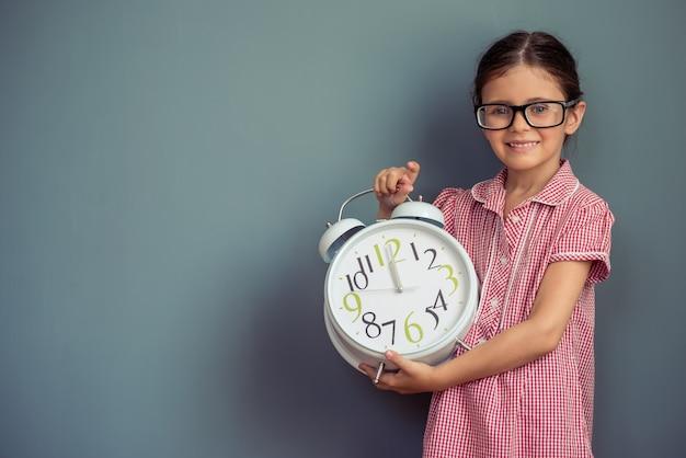 Девушка в милом платье и очках держит будильник