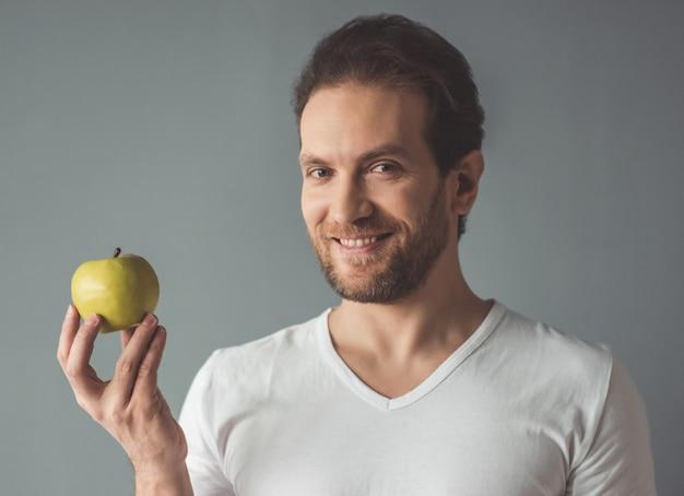 ハンサムな男はリンゴを保持しています。