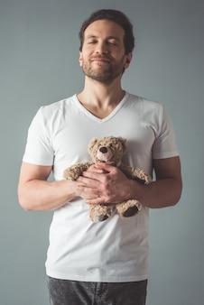 Мужчина держит плюшевого мишку и улыбается с закрытыми глазами