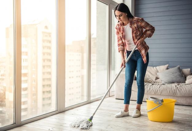 美しい若い女性は床を掃除しながら笑っています。