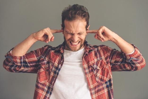 カジュアルな服装の若い男が彼の耳を覆っています。