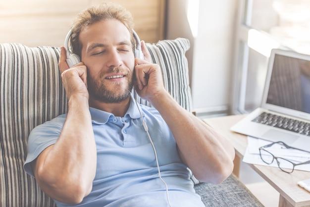 カジュアルな服装でハンサムな男は音楽を聴いています