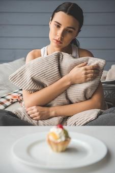 女の子はソファに座ってケーキを悲しげに見ています。