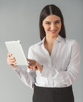 フォーマルな服装の女性はデジタルタブレットを使用しています