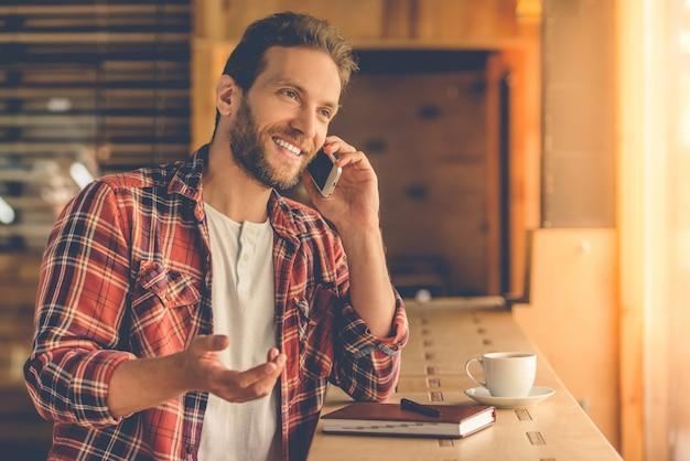 ハンサムなデザイナーは携帯電話で話しています