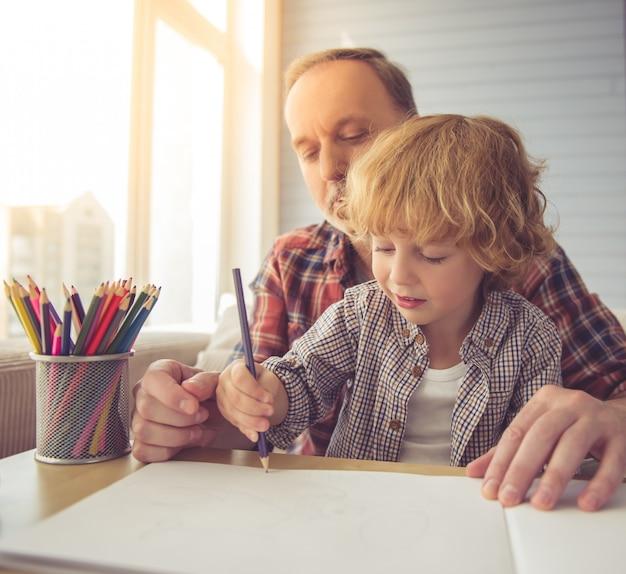 Красивый дедушка и внук рисуют вместе