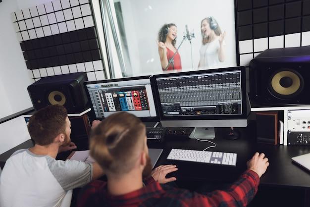 Две девушки поют в студии звукозаписи.