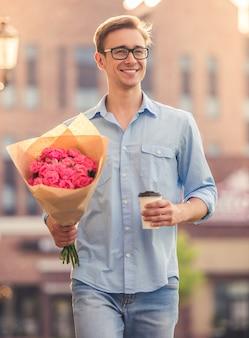 ハンサムな男は花とコーヒーを保持しています。