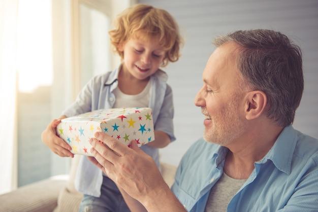 かわいい男の子は彼のおじいちゃんに贈り物を与え、笑顔