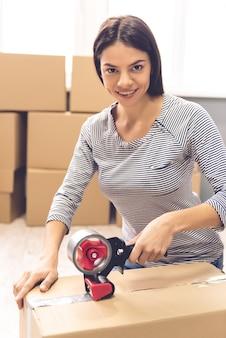 Девушка упаковывает движущуюся коробку с помощью клейкой ленты