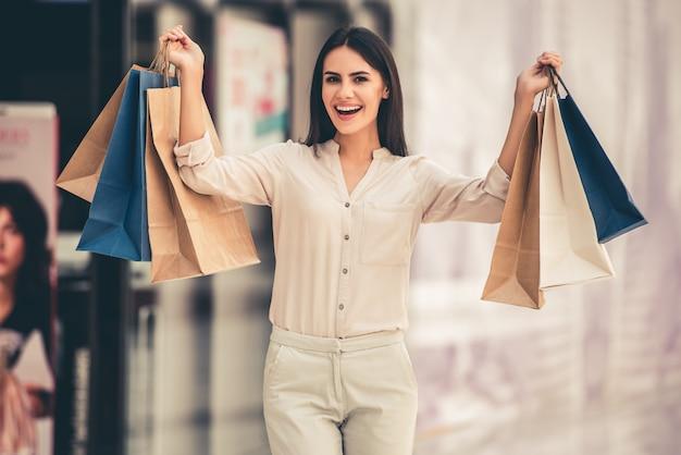 美しい少女は買い物袋を保持しています。