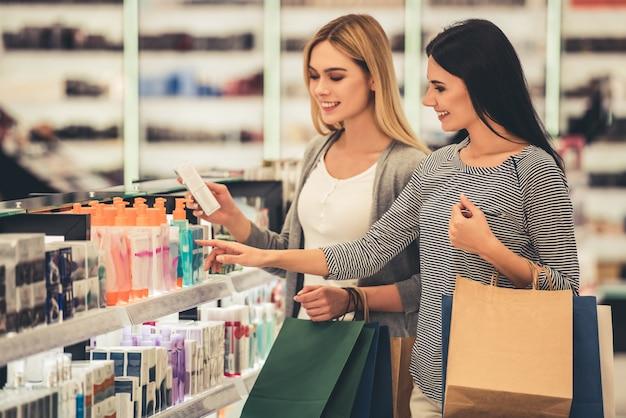 買い物袋を持つ美しい女の子は化粧品を選択しています