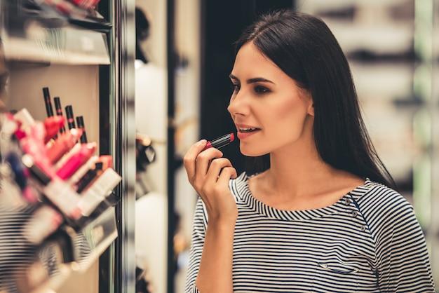 Девушка выбирает помаду, делая покупки в торговом центре