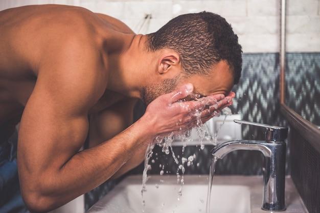 浴室で身を洗うアフロアメリカ人