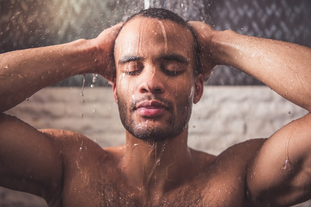 裸のアフロアメリカ人は浴室でシャワーを浴びています。