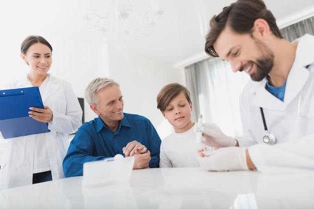 資格のある医者が子供の指から血を取ります。