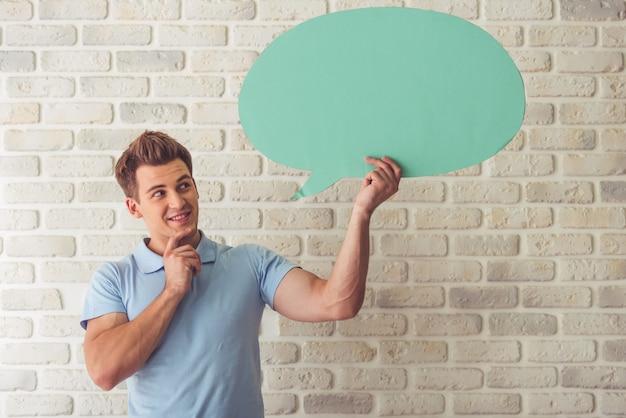 Мускулистый парень в синей футболке держит пузырь речи
