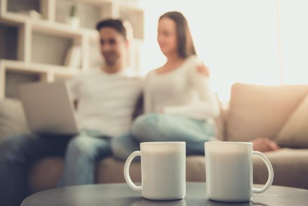 若いカップルは自宅のソファに座ってラップトップを使用しています