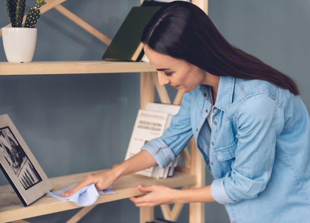 女性は自宅で家具を掃除しながらぼろを使用しています