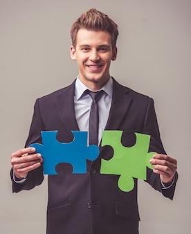 スーツのビジネスマンはパズルのピースを保持しています。