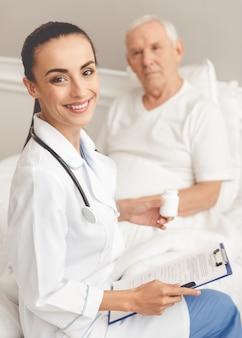白い医療コートの医者は薬の瓶を保持しています。