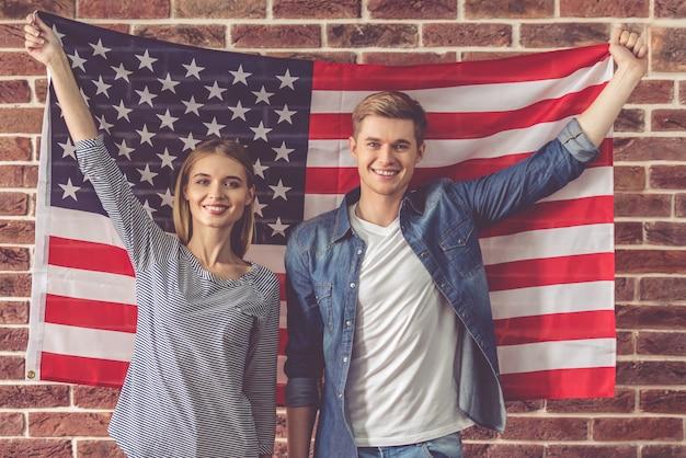 美しい若いカップルはアメリカの国旗を保持しています。