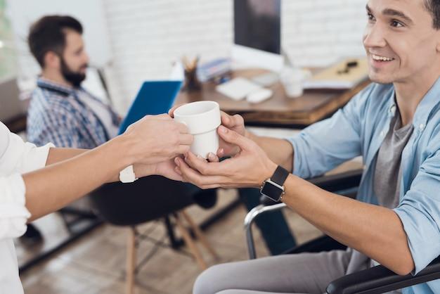 オフィスの車椅子の男にカップを与える女性。
