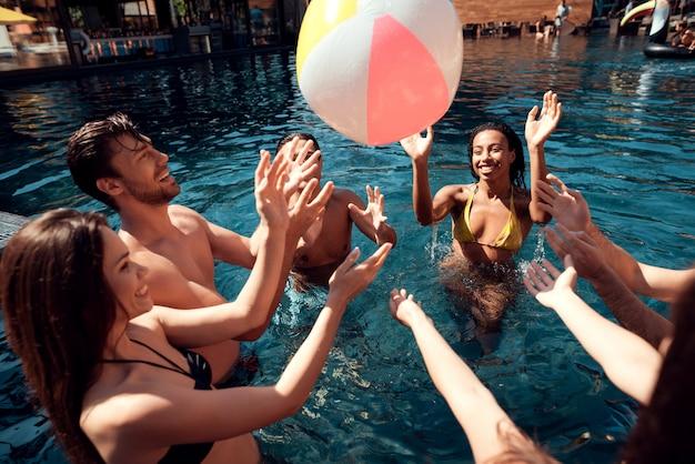プールで楽しんでいる若い笑顔の友人のグループ