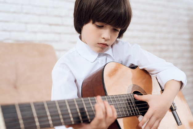 白いシャツの黒髪の少年がギターを弾いています。