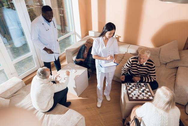 老人ホームで年配の男性と女性がチェスをしています。
