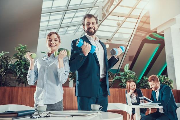 オフィスでダンベル運動をする労働者。