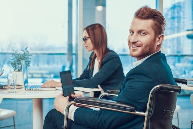 オフィスでタブレットで車椅子のスーツを着た労働者。