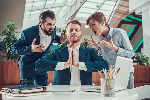 Люди кричат на медитирующего работника в костюме в офисе.