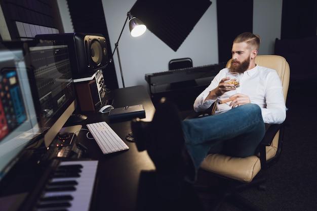 Мужской продюсер сидит в студии звукозаписи.