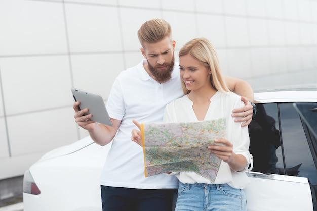 Молодой парень и девушка смотрят на карту автомобильных дорог.