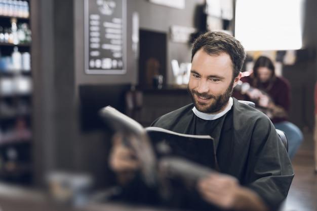 Мужчина сидит в парикмахерской и выбирает прическу в каталоге.