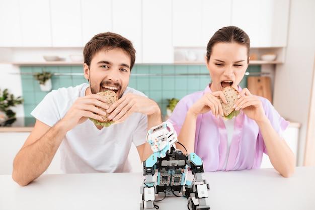 若いカップルが台所に座って食べています。