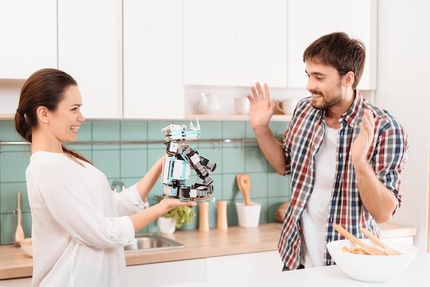 女の子は彼にサイのロボットを与えましたが、男は興奮しています。